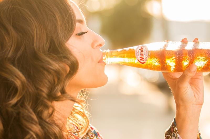 woman drinking orange liquid from bottle