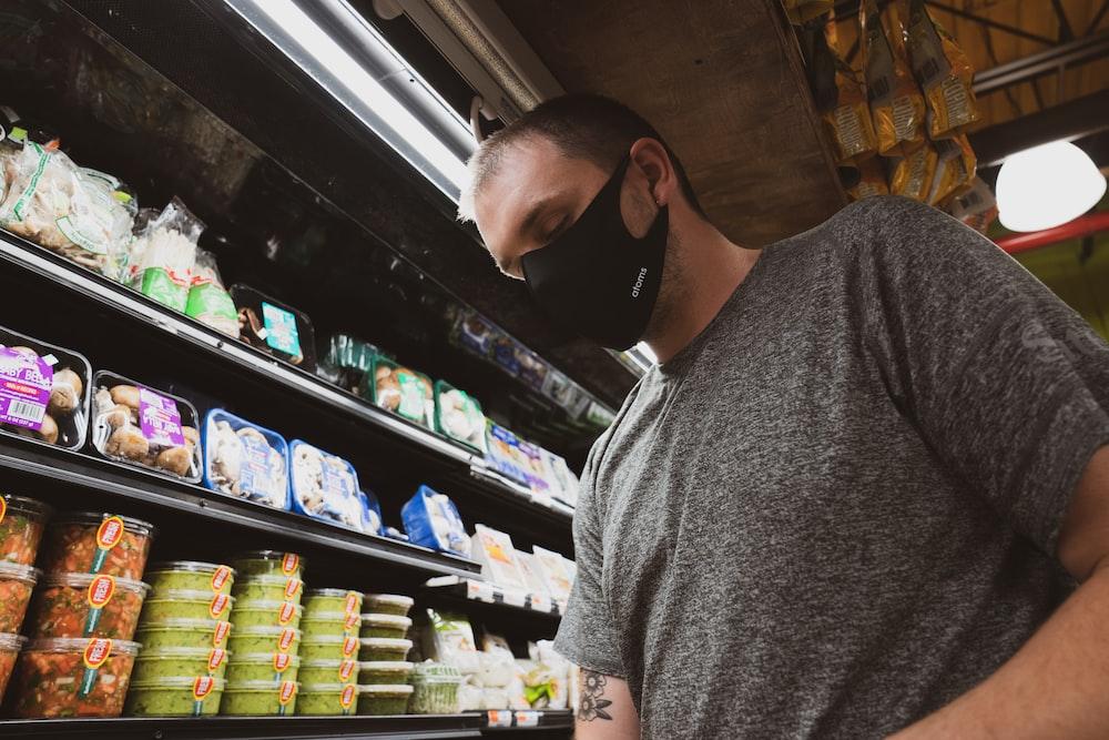man in gray crew neck t-shirt standing near shelf
