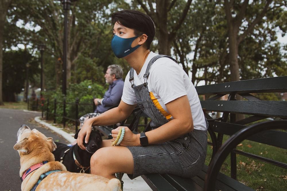 man in white t-shirt and black shorts sitting on black bench during daytime