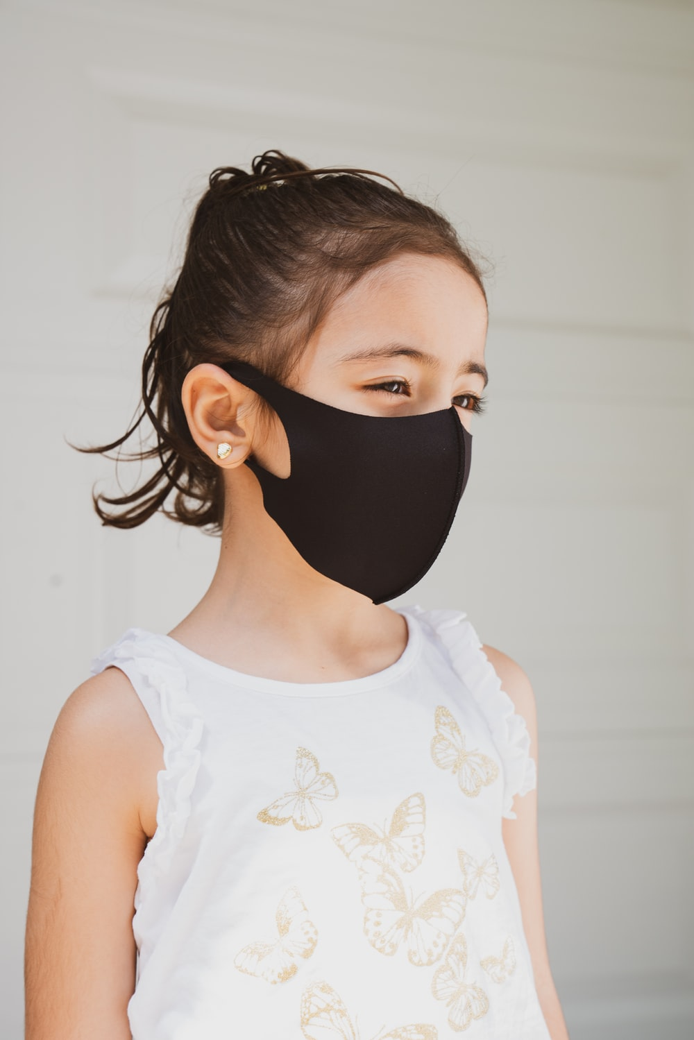 woman in white floral tank top wearing black mask