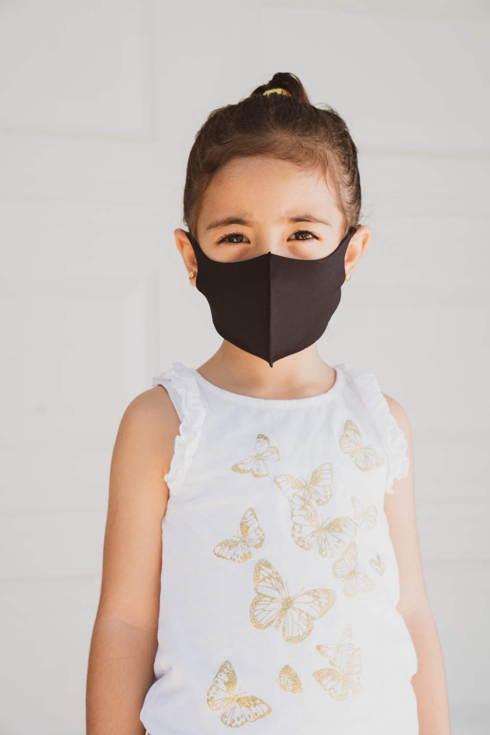 girl in white floral tank top wearing black face mask
