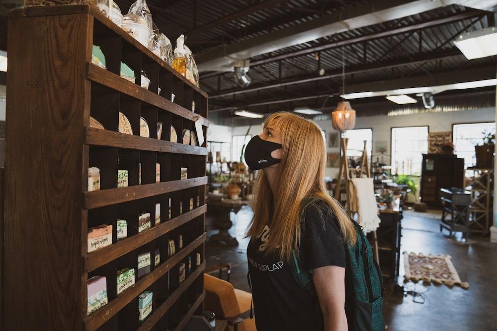 woman in black t-shirt standing near brown wooden shelf