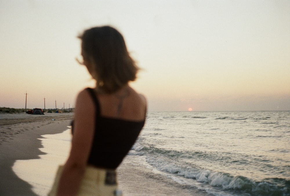 woman in black tank top standing on beach during daytime