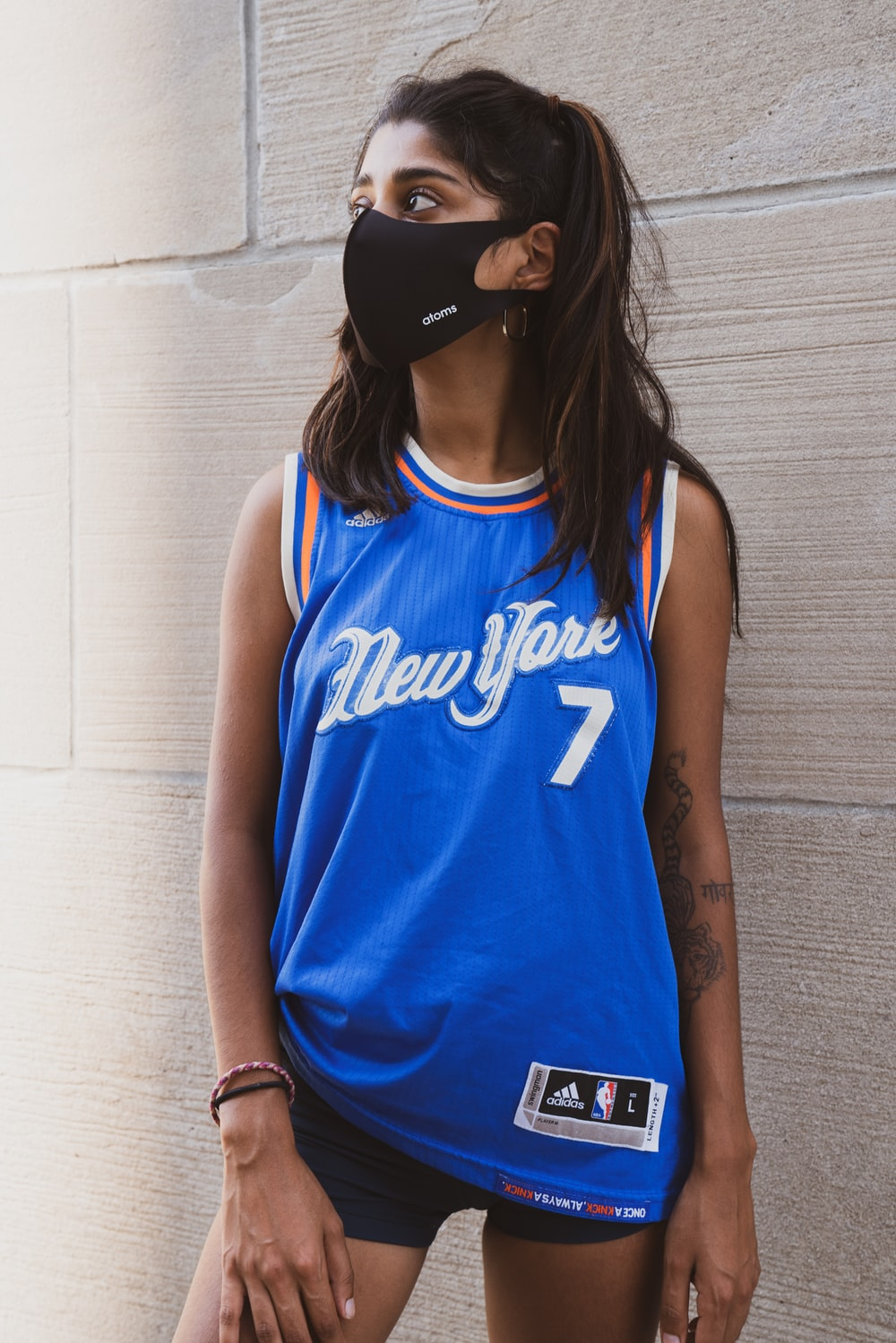 woman in blue and white tank top wearing black cap