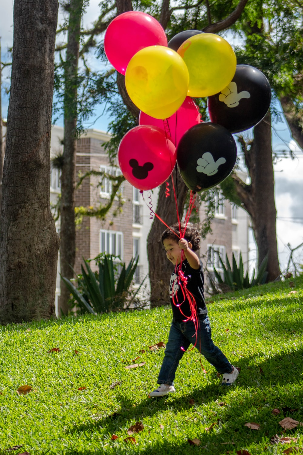 girl in red and black jacket holding balloons