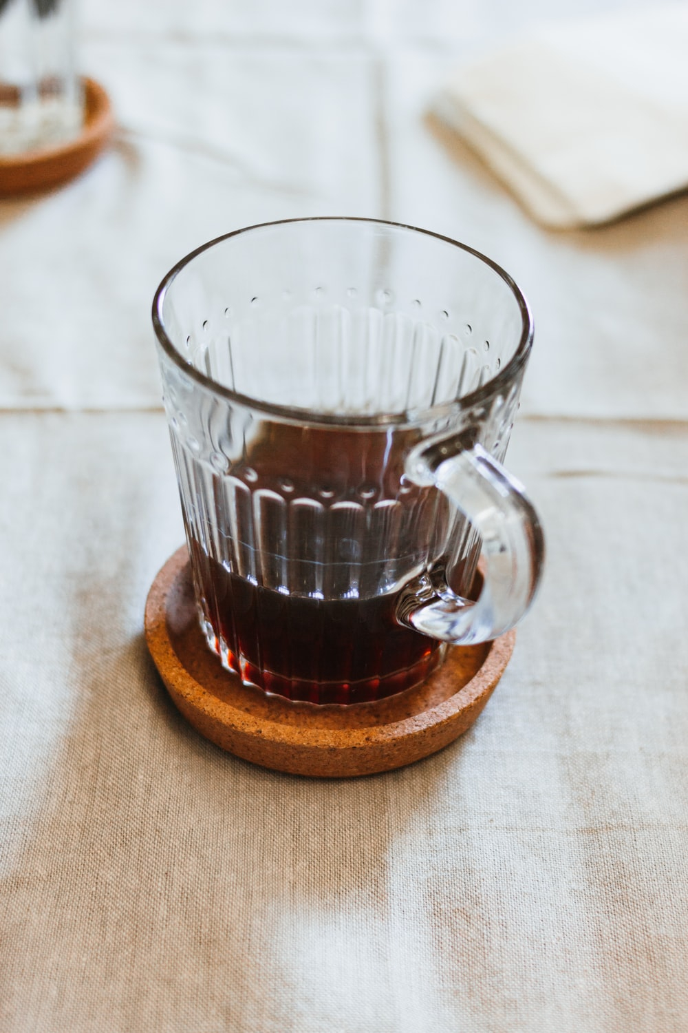 clear glass mug on brown coaster