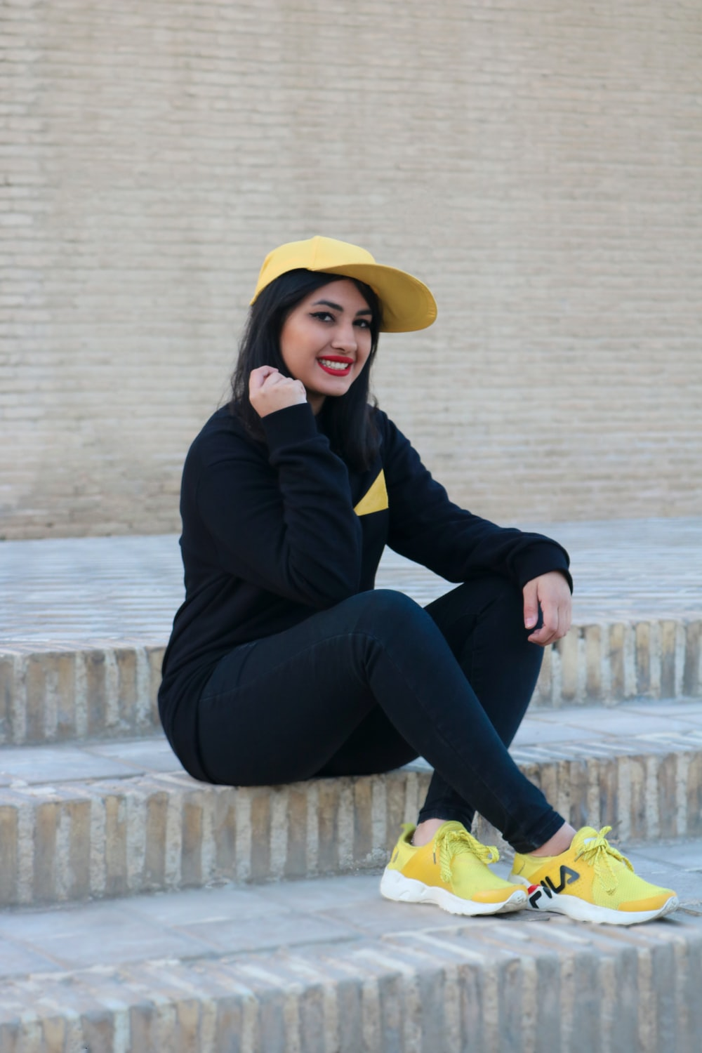 woman in black jacket and yellow sun hat sitting on concrete stairs