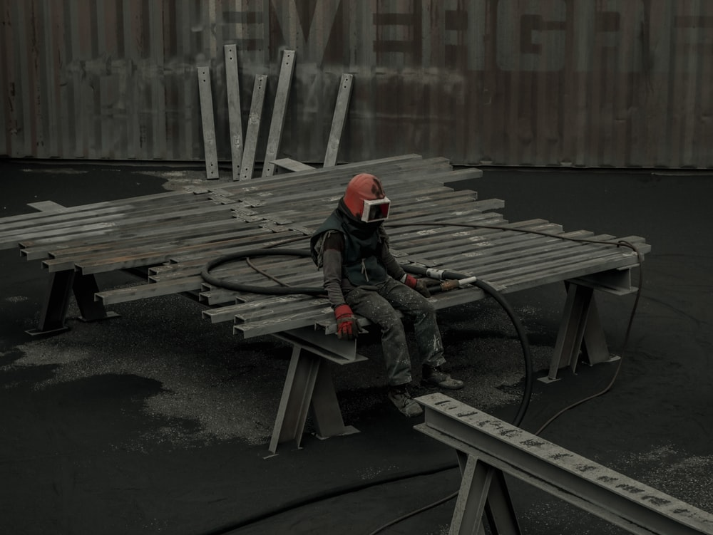 man in black jacket and red helmet sitting on brown wooden bench