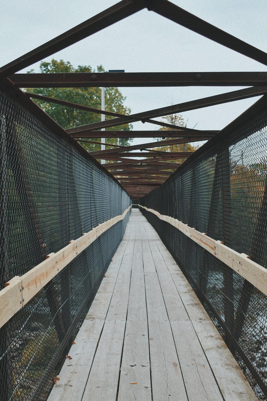 brown wooden bridge with green metal fence