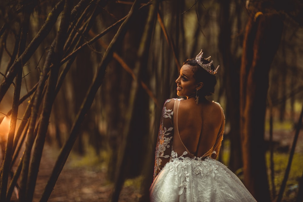 woman in white floral dress standing in woods