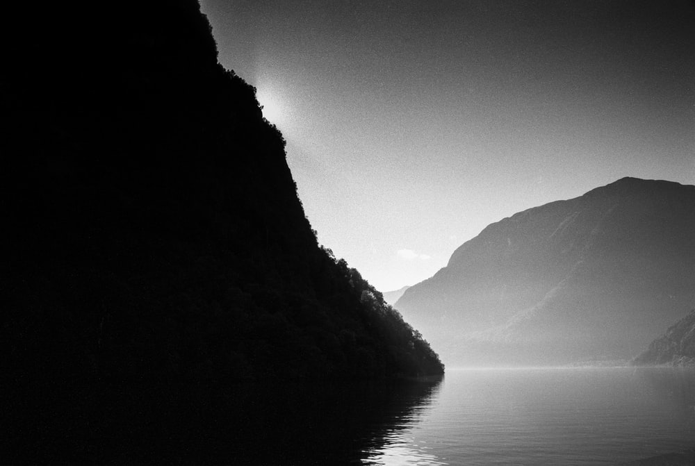 grayscale photo of lake between mountains