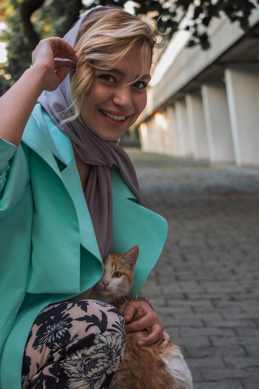 woman in green coat holding brown tabby kitten