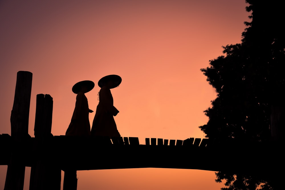 silhouette of man and woman statue during sunset