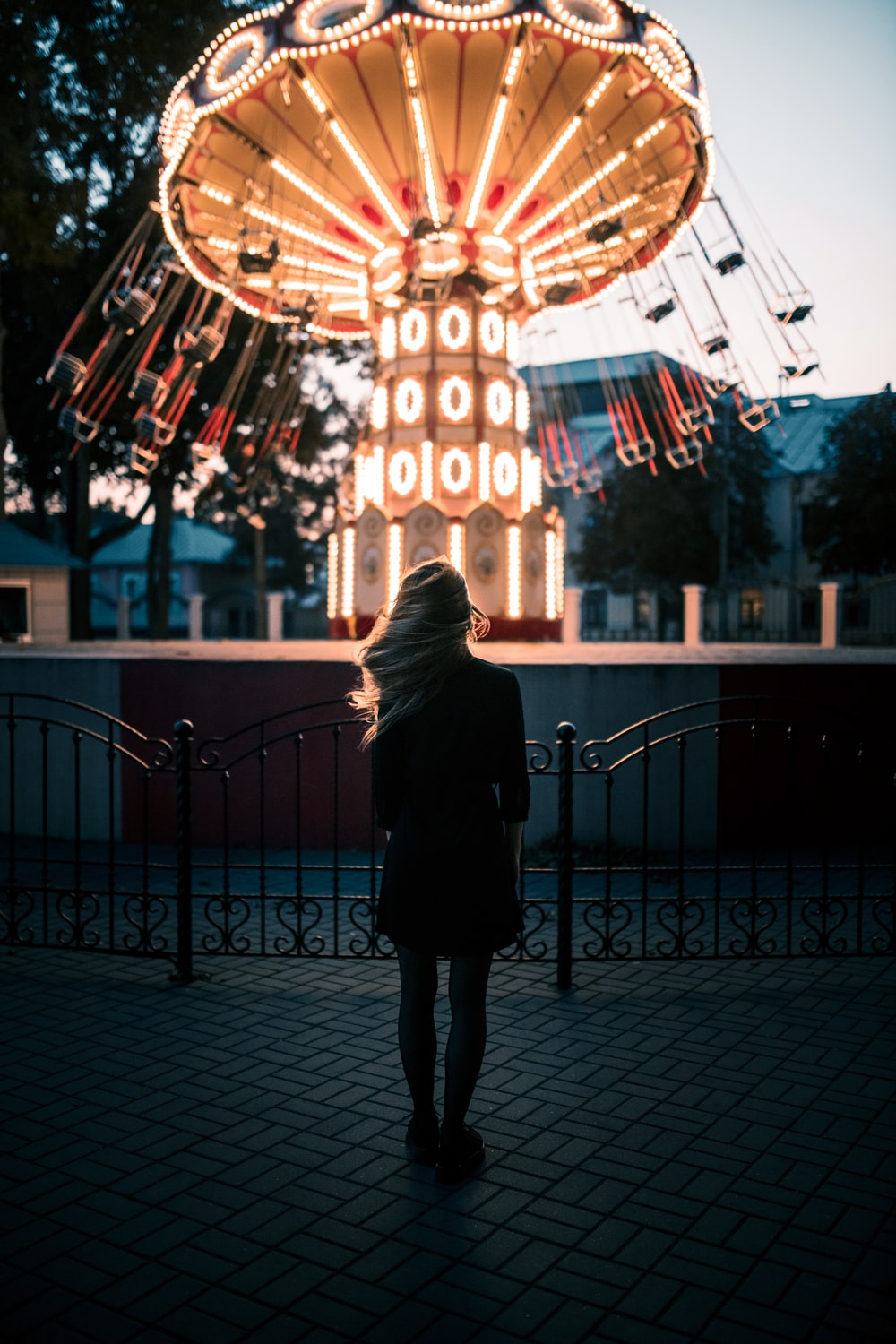 woman in black coat standing in front of lighted building