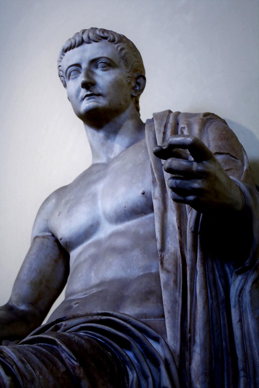 man statue near white wall