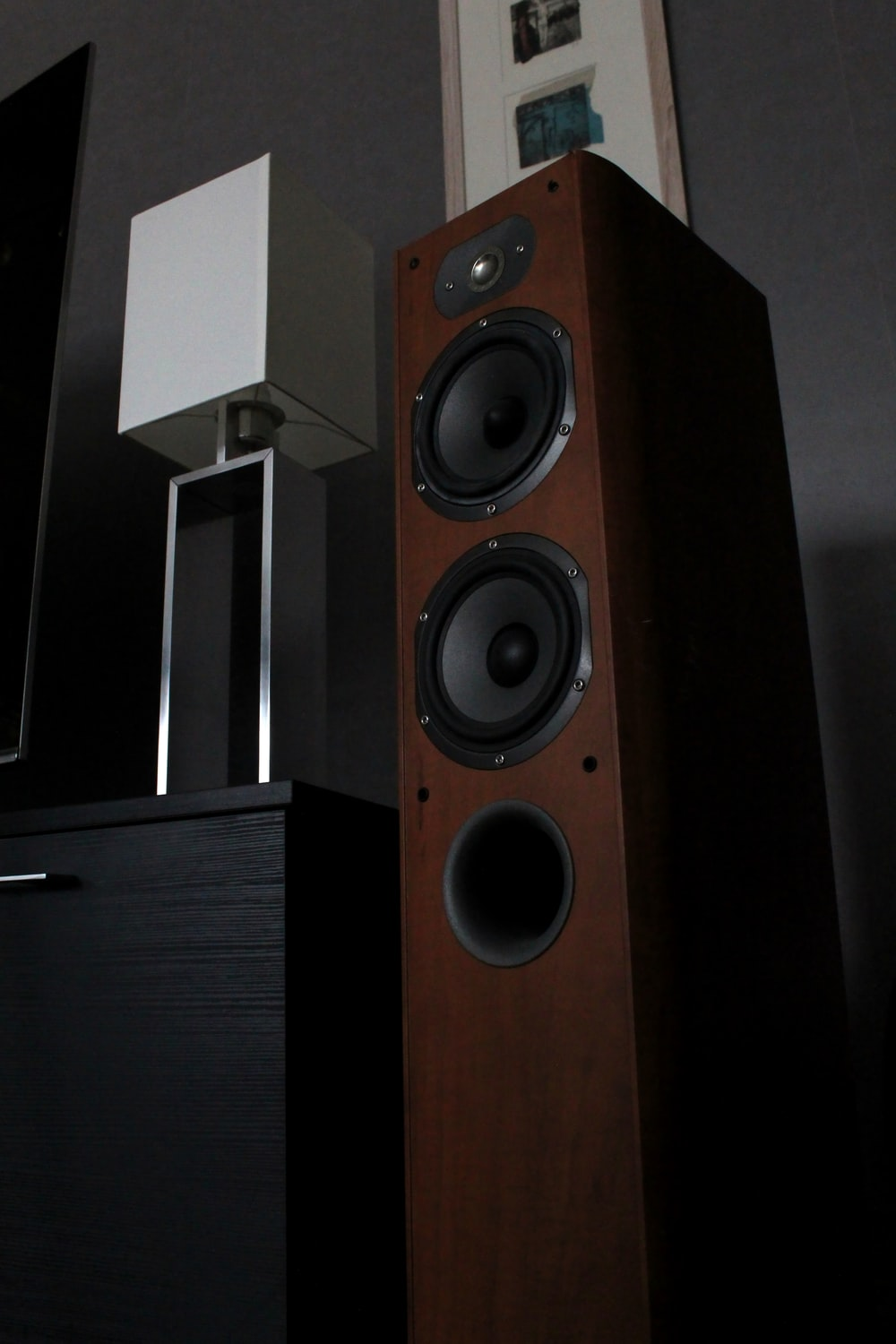black and silver speaker on brown wooden cabinet