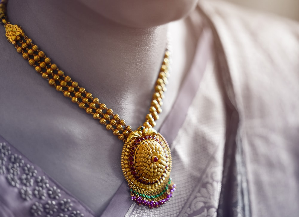 person wearing gold and silver necklace