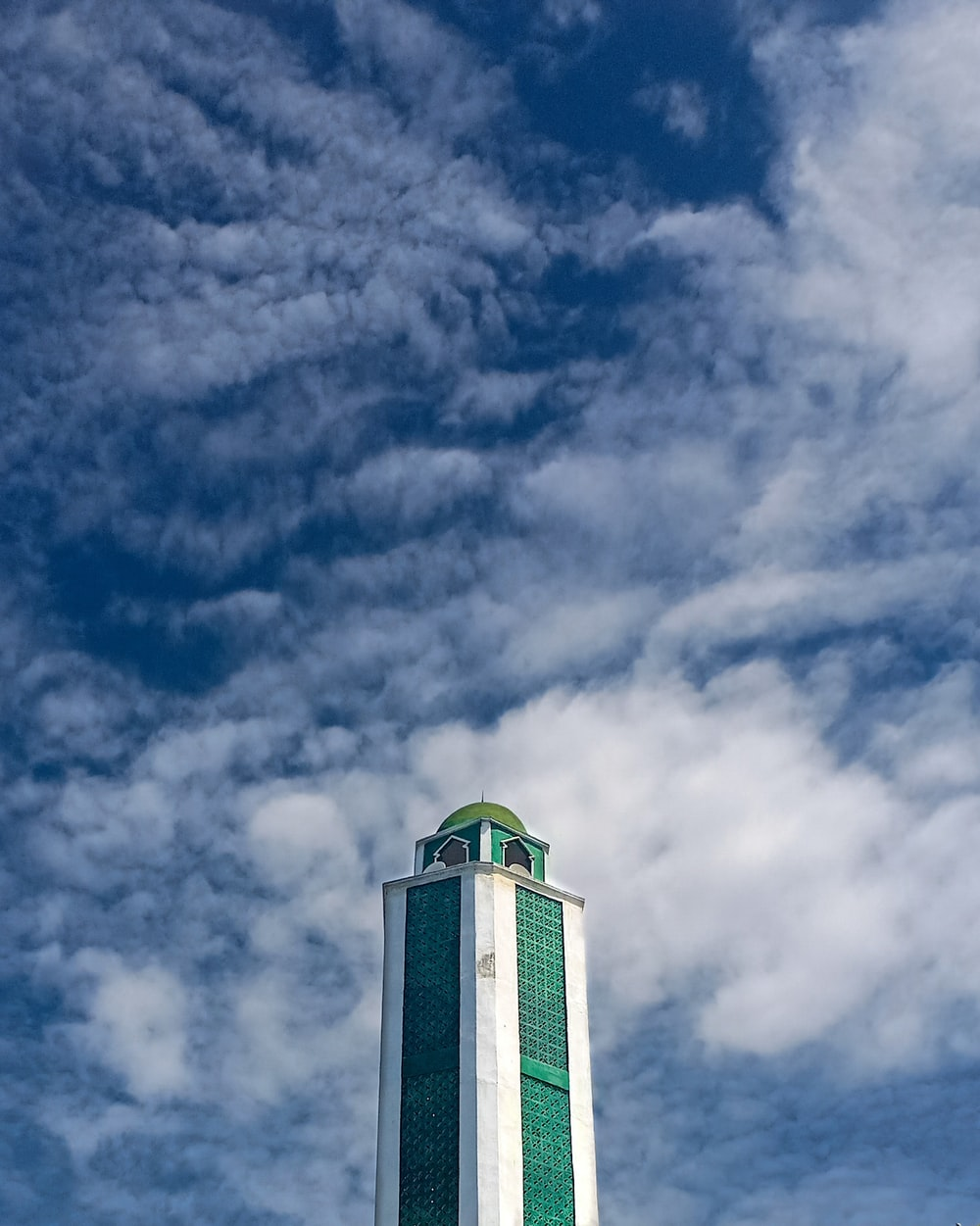 white and green concrete building under blue sky