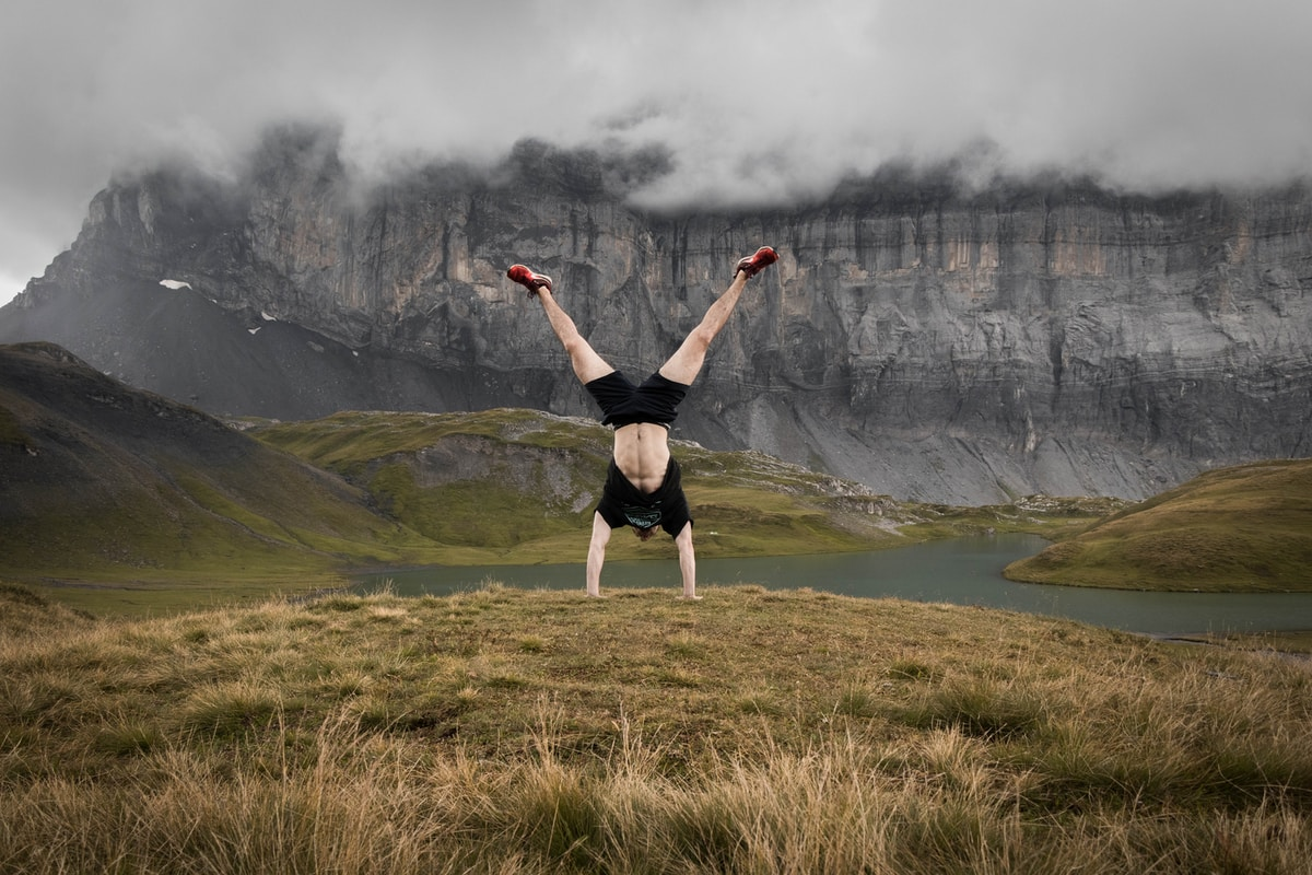 hiker doing a handstand outdoors