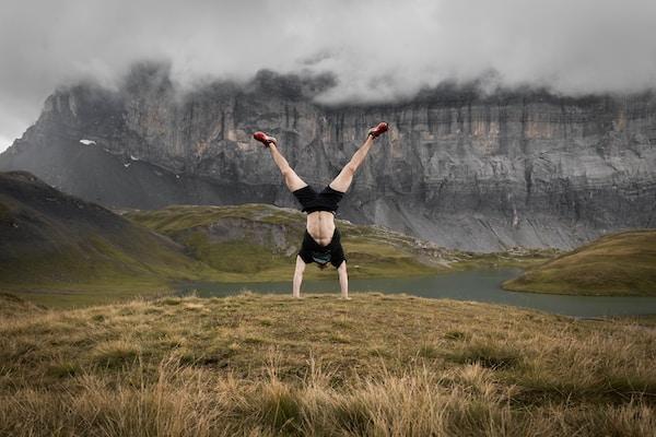 hiker doing a handstand outdoors