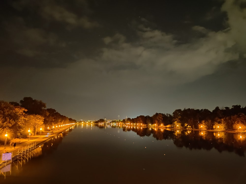 body of water near city buildings during night time
