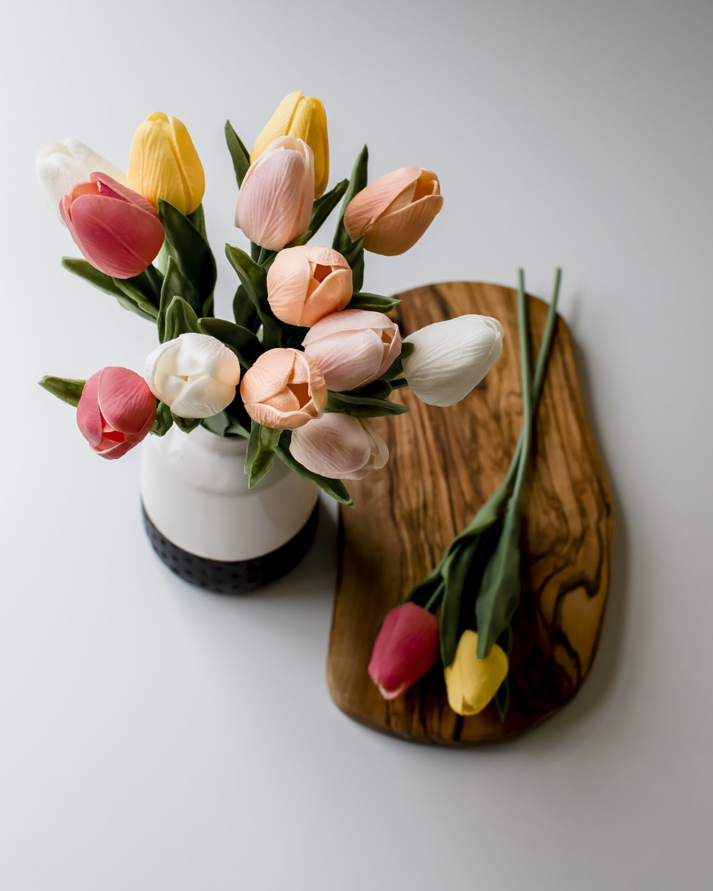 pink and white tulips in white and brown ceramic vase