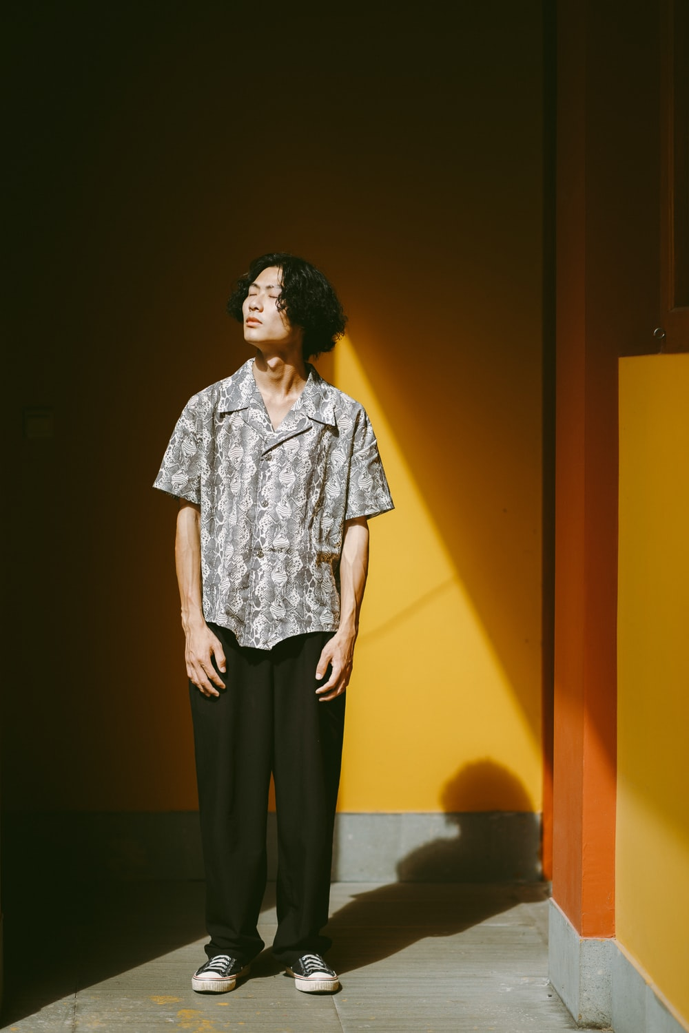 woman in white and black button up shirt and black pants standing beside yellow wall