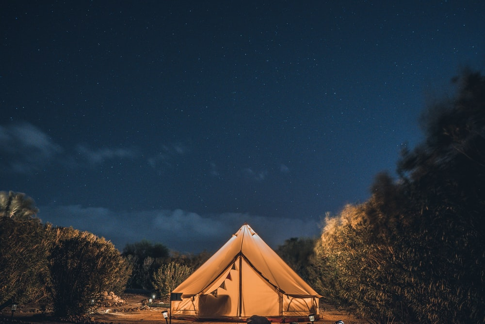 brown and white tent under blue sky during night time