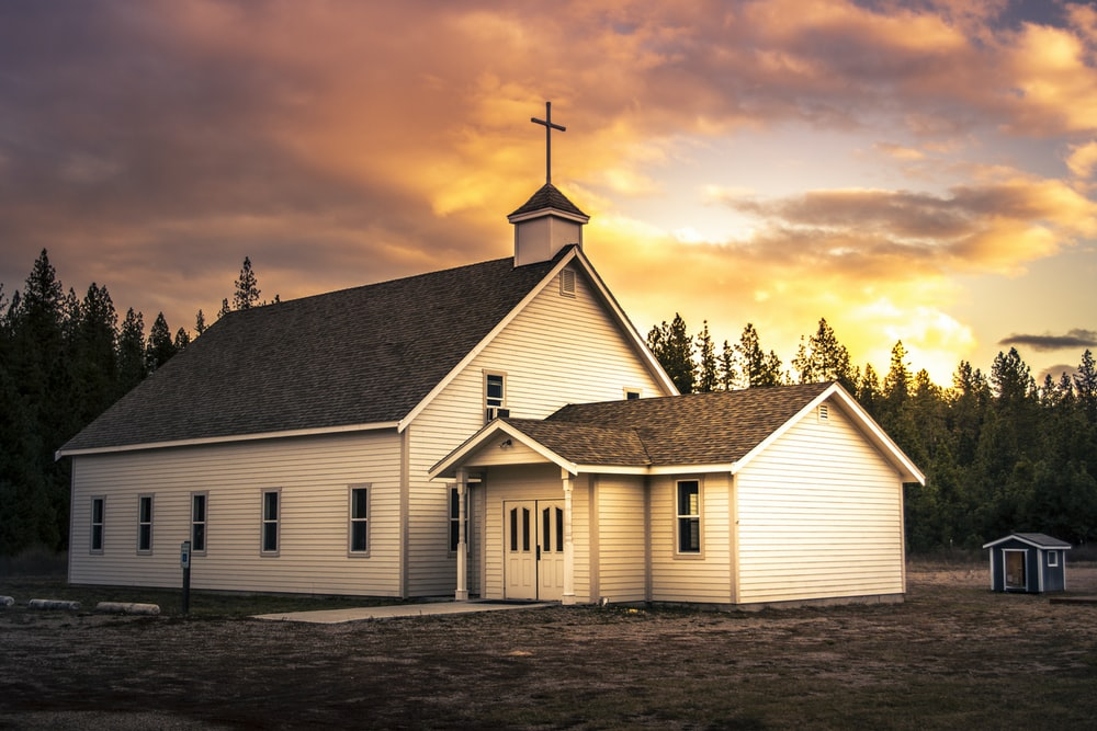 white and brown wooden church under cloudy sky during daytime