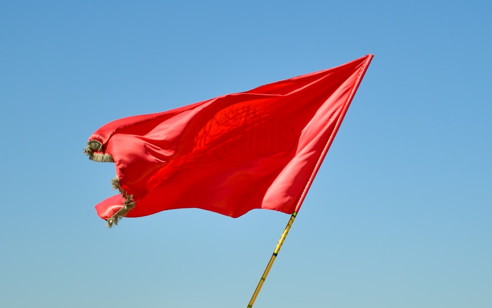 red flag on pole under blue sky during daytime