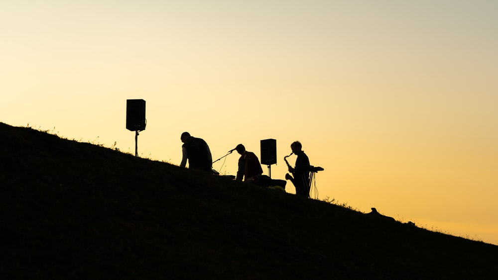 silhouette of people standing on hill during sunset