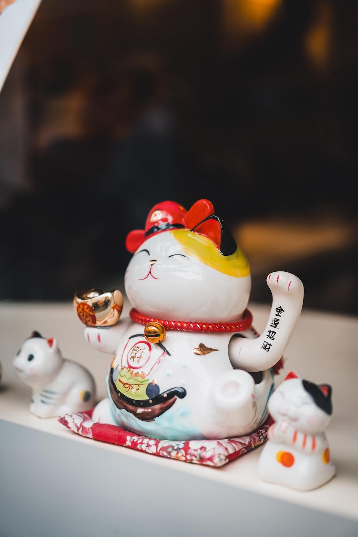 white and red ceramic cat figurines