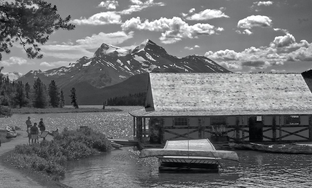 grayscale photo of a lake near a snow covered mountain