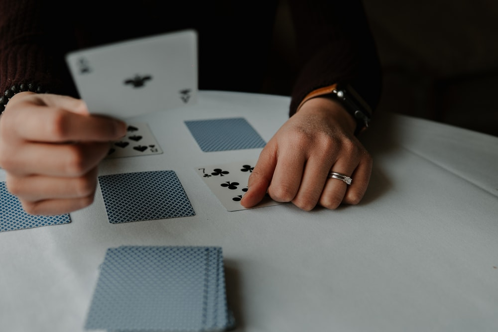 person holding playing cards on white table