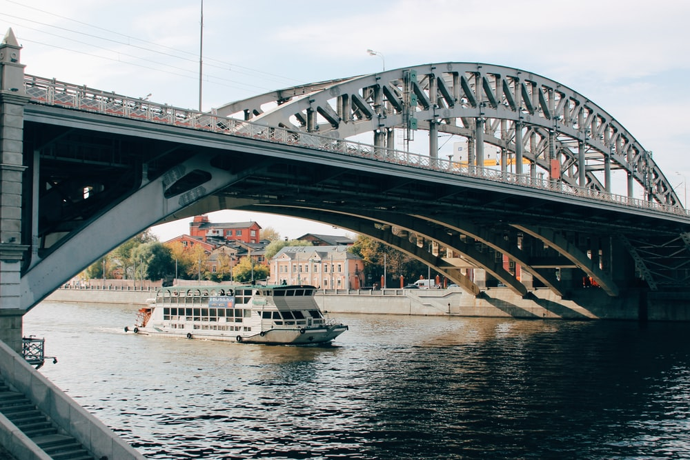 white and black boat on body of water under bridge during daytime