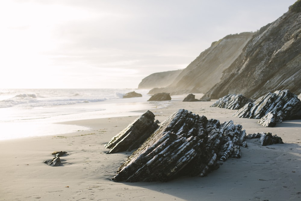 brown rock formation on white sand beach during daytime