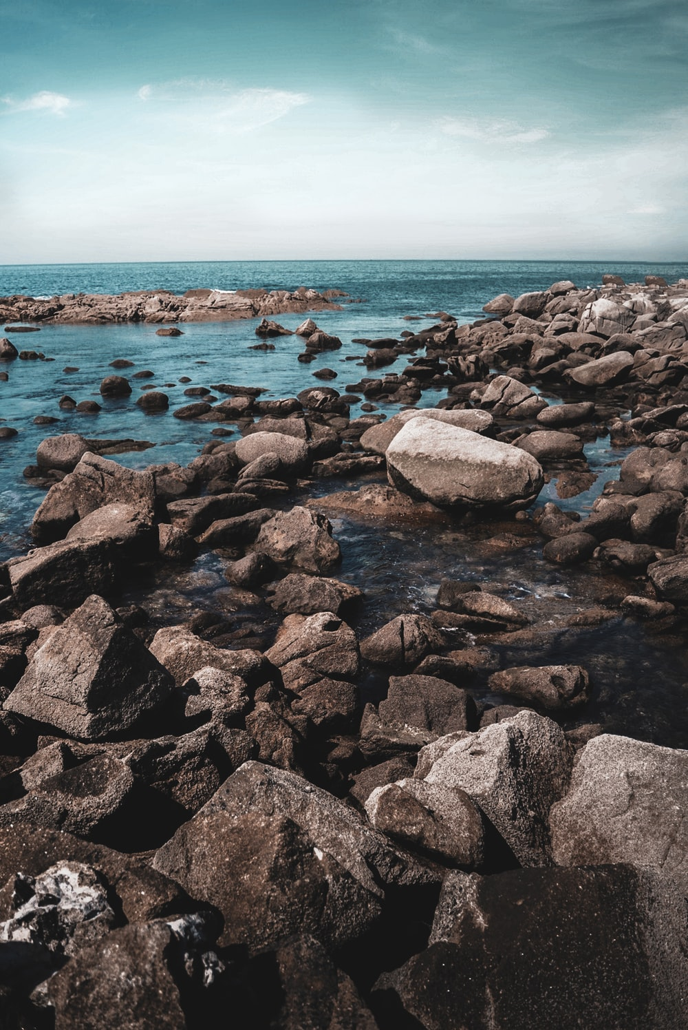 gray and black rocks on sea shore during daytime
