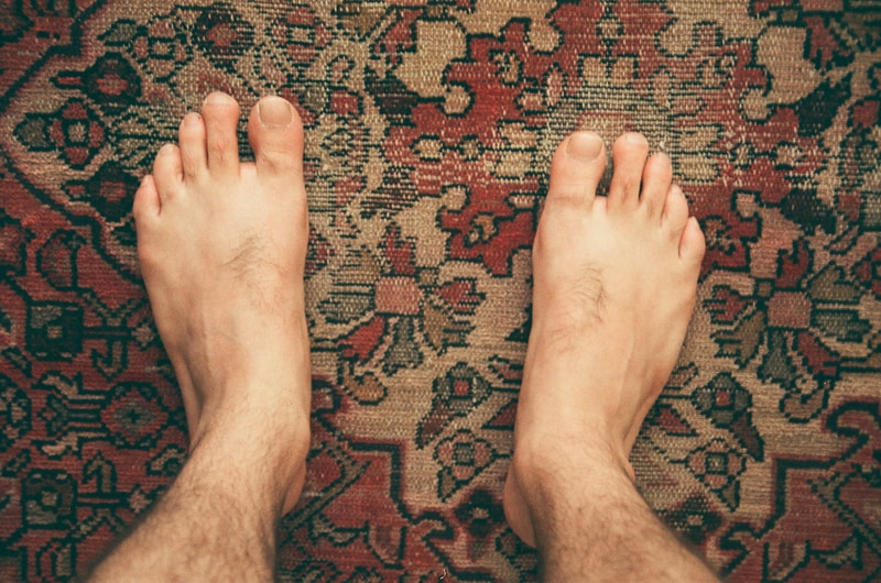 persons feet on red and brown area rug