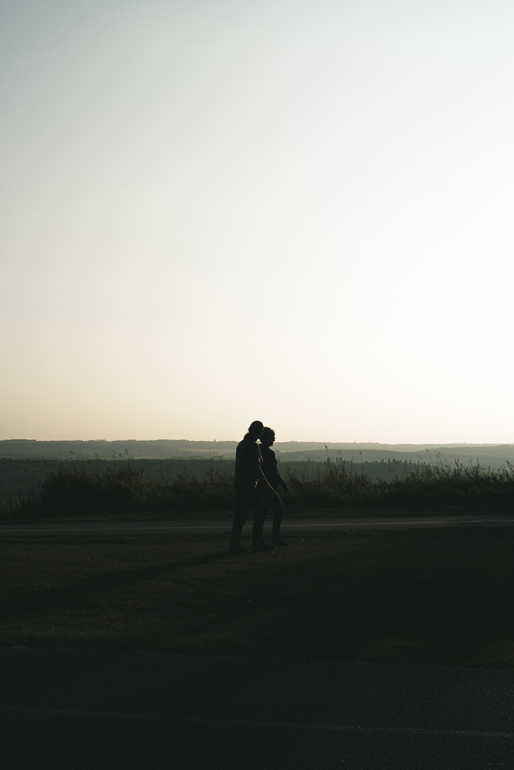 silhouette of man standing on grass field during daytime