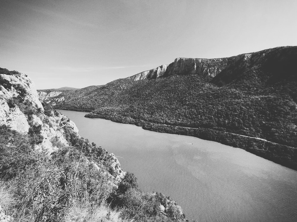 grayscale photo of river between mountains