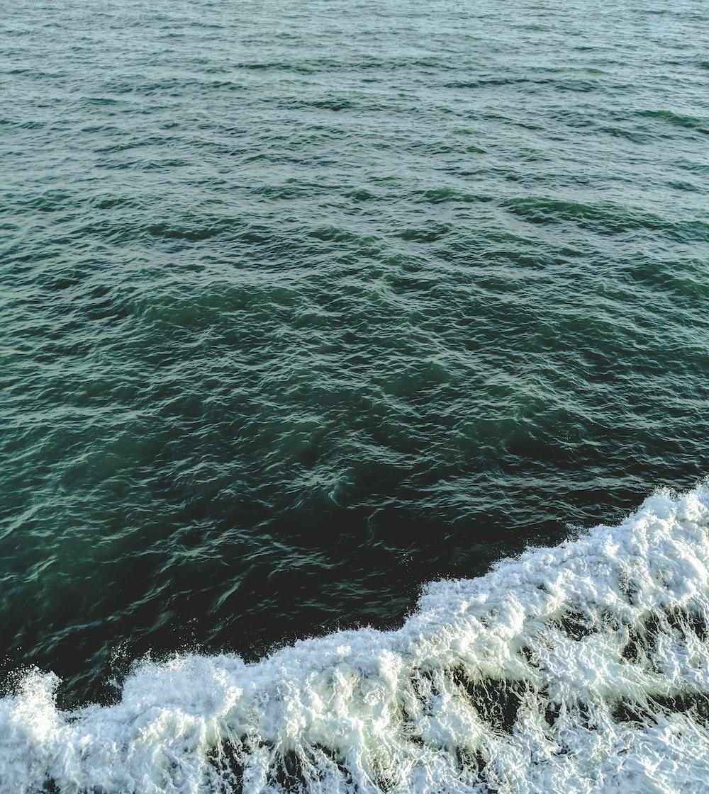 body of water near gray rocks during daytime