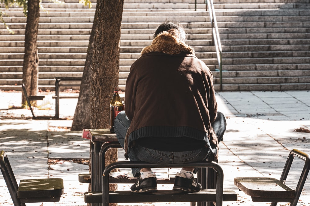 man in brown jacket sitting on chair