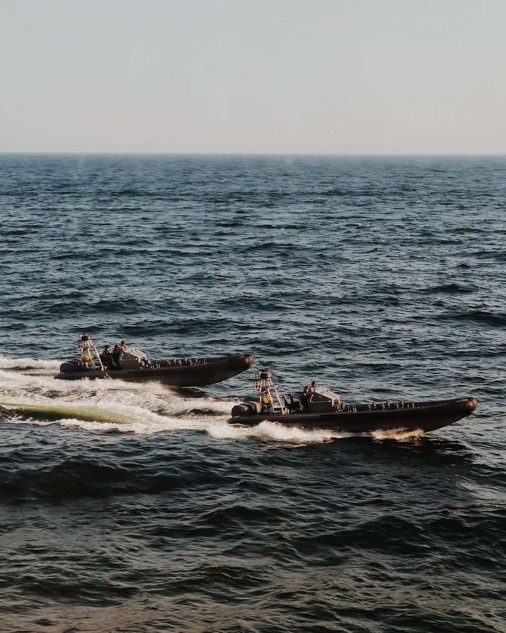 people riding on white and black boat on sea during daytime