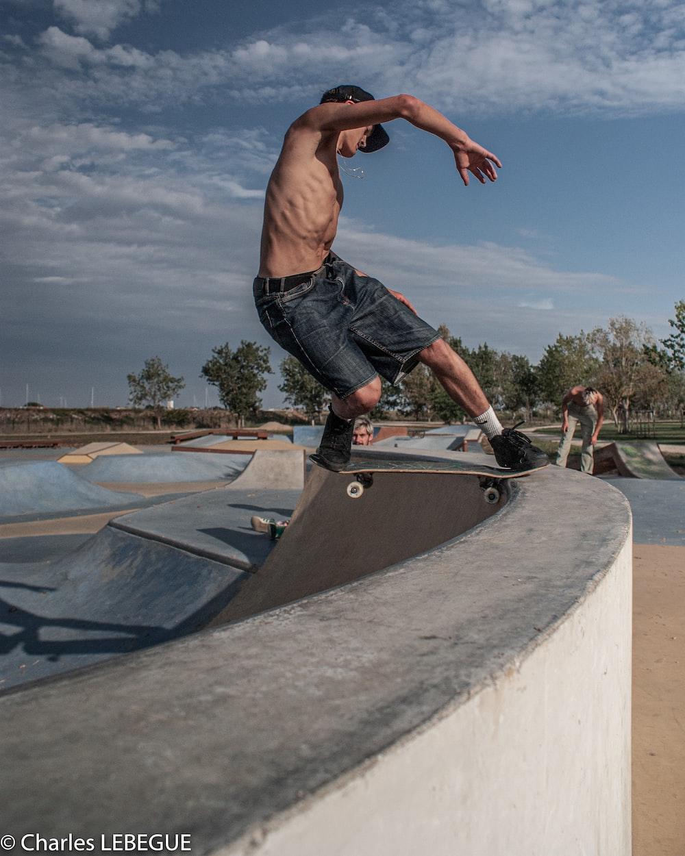 man in black shorts doing skateboard stunts on skateboard ramp during daytime