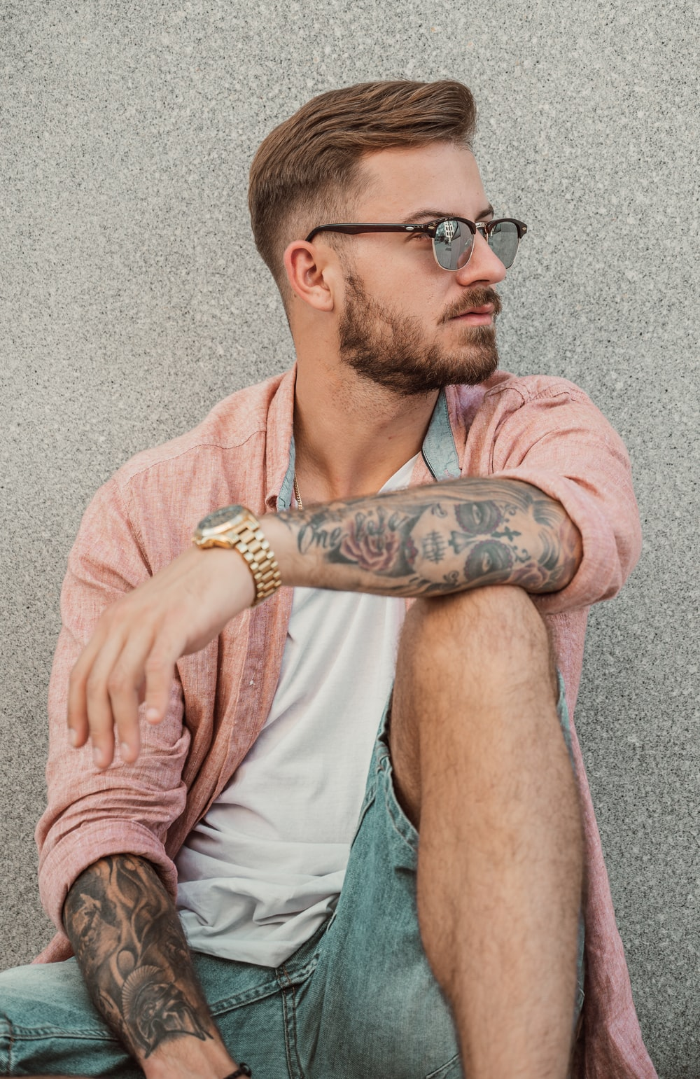 man in pink polo shirt with black sunglasses and black tattoo on his right arm
