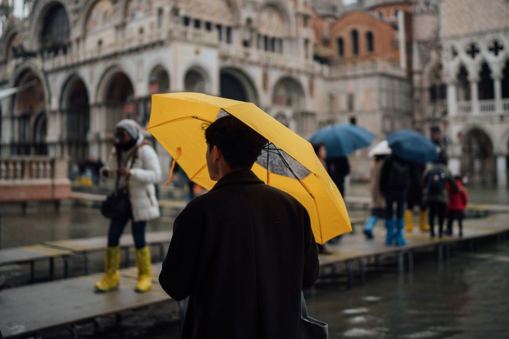 man in black coat holding yellow umbrella