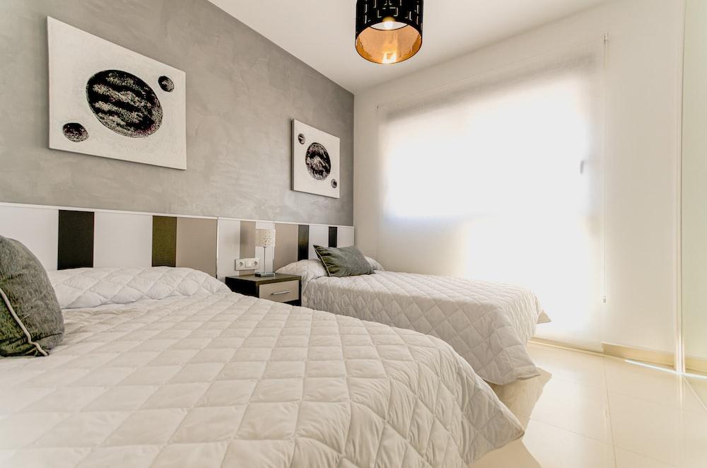 white bed linen near white wall
