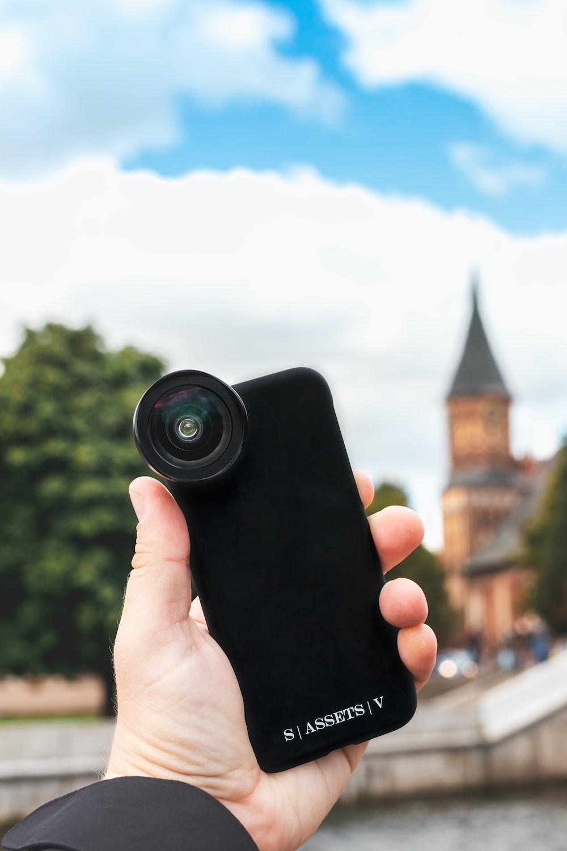 person holding black camera lens