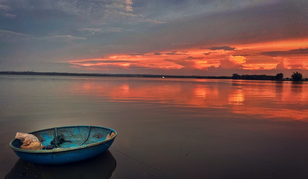 blue and white boat on water during sunset