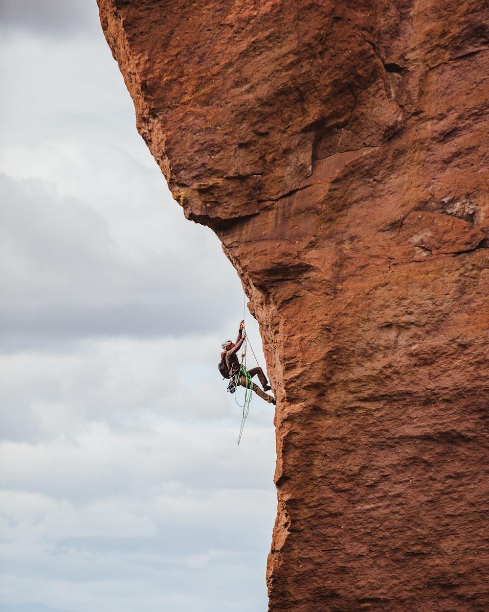 man in black shorts climbing brown rock formation during daytime